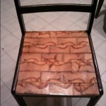 Found chair frame without a seat. I cut out a seat for it and made a mosaic of salvaged wood slices.